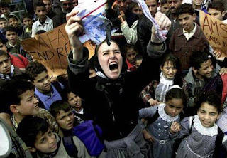 "Photo: Rachel Corrie screaming while burning a US flag before a group of ""Palestinian"" children"