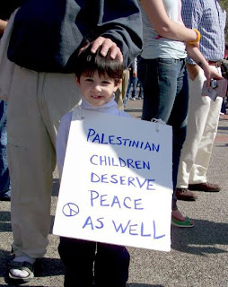 "Photo: Child holding placard saying, ""Palestinian children deserve peace as well"""