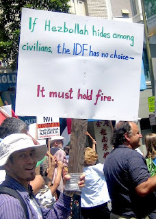 "Photo: Moonbat demonstrator during the 2006 Lebanon War holding a sign saying, ""If Hezbollah hides among civilians, the IDF has no choice--it must hold fire."""