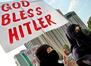 "Photo: niqab-clad Muslim women holding a sign that says, ""God Bless Hitler"" (accursed be those who think such evil thoughts)"
