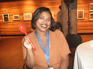 a woman smiling holding a red Betty Crocker Spoon