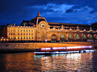 evening photo of musee d'orsay at night lights shining and boat on river seine