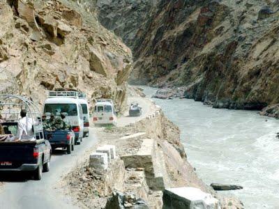 Vehículos pasando al lado de un caudoloso río en la Karakoram Highway