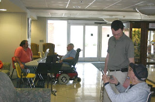 Justin Dickson (foreground) and Jonathan Eller (background) talking with residents of the NC Veterans Home