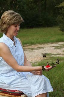 A lady hand-feeding hummingbirds
