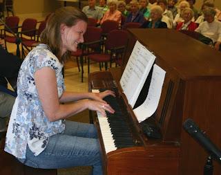 Sara Dickson playing piano at Trinity Oaks Retirement Community