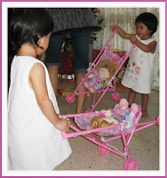 Our twin grand-daughters enjoying their new toy stroller