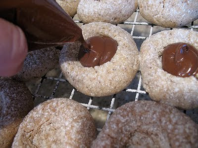 A close up photo of Nutella being piped onto the thumbprint cookies.