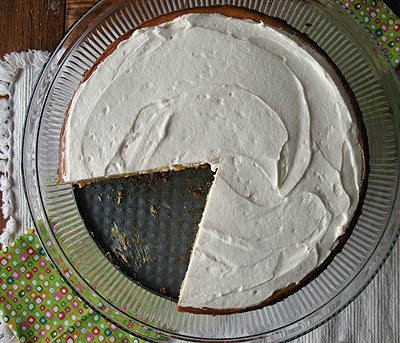 An overhead photo of a pumpkin cheesecake with rum whipped topping with a slice missing.