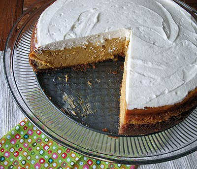 A photo of a pumpkin cheesecake with rum whipped topping with a slice missing.