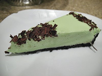 A close up photo of a slice of grasshopper pie on a white plate.