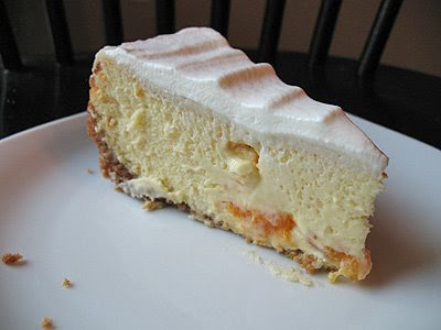 A close up photo of a slice of mandarin orange cheesecake on a plate.
