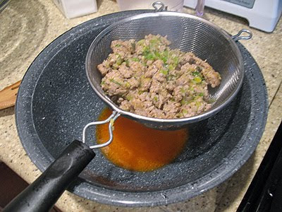 A close up photo of cooked sausage, shallots, and garlic in a strainer over a bowl to drain the excess fat.