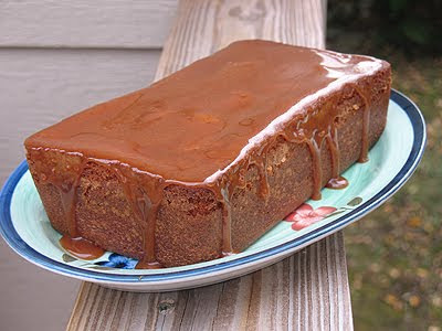 A photo of an apple cider pound cake with caramel glaze resting on a plate.