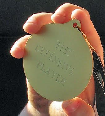A close up photo of Dominic\'s award for best defensive player.