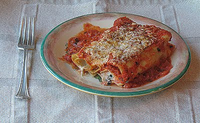A close up photo of a serving of baked manicotti with prosciutto on a plate.