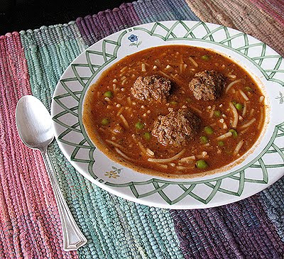 A close up photo of a bowl of Amanda\'s meatball soup with a spoon resting on the side.
