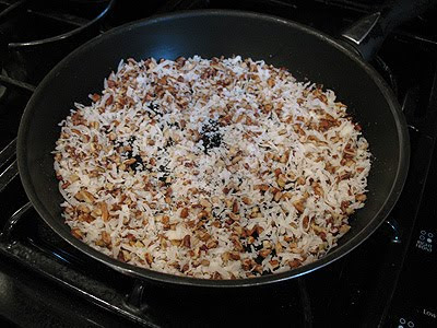 A photo of a skillet of coconut and pecans.