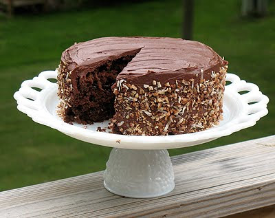 A photo of a chocolate sauerkraut cake with a slice missing on a white cake stand.