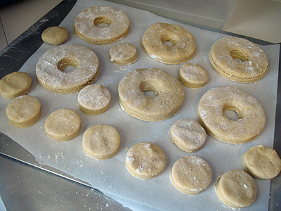 A photo of apple cider doughnut dough cut into shapes resting on a baking sheet.