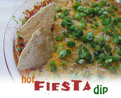 A close up photo of two tortilla chips being dipped in hot fiesta dip.