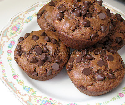A close up photo of a stack of chocolate chocolate chip muffins resting on a plate.