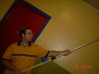 Drew painting the ceiling and smiling at the camera at the Metro House on 18 December 2006